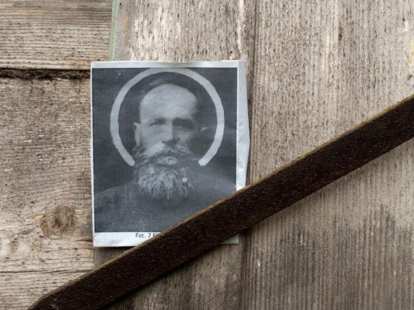Fotografia Eliasza Klimowicza wetknięta za okiennicę domu.